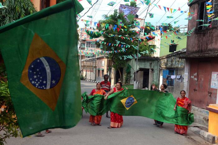 Ladies in Kolkata display giant flags of Brazil, ahead of the World Cup opener. (Source: IE Photo by Partha Paul)