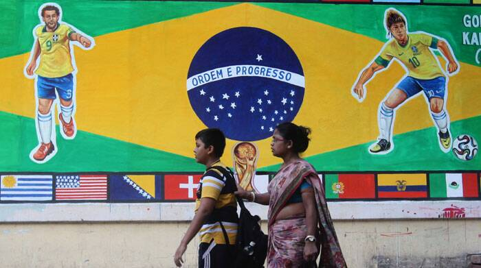 People walk through a lane in South Kolkata adorned with paintings of Brazil's players Neymar and Fred. (Source: IE Photo by Partha Paul)