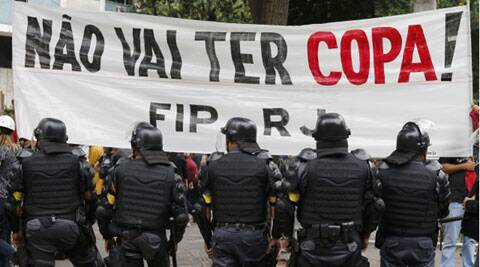 "Police officers stand guard in front of a banner during a protest against the 2014 World Cup in Rio de Janeiro. The banner says: ""There won't be a World Cup"". (Source: Reuters)"