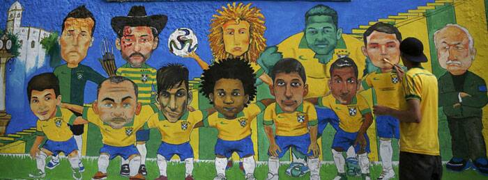 An artist paints a wall mural of the Brazilian national football team and coach Luiz Felipe Scolari ahead of the World Cup. Brazil will take on Croatia in the tournament opener on Thursday. (Source: Reuters)
