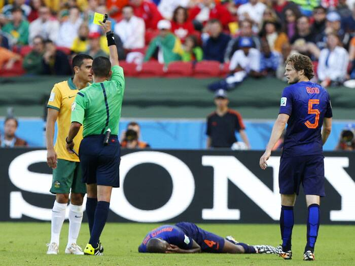 Algerian referee Djamel Haimoudi, showed a yellow card to Australia's Tim Cahill (L) after Cahill's collision with Netherlands' Bruno Martins Indi. (Source: AP)