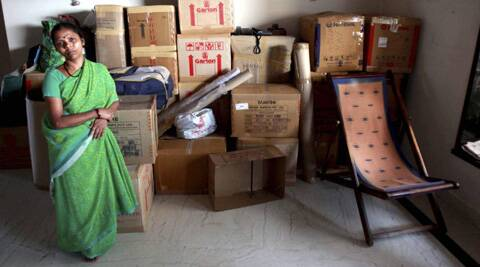 A woman waits near luggage to vacate a residential flat in the Campa Cola society at Worli in Mumbai ahead of forceful eviction and demolition as per SC order. (Source: PTI)