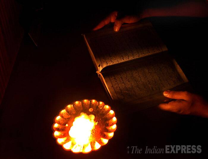 A person is seen reading the holy Quran in candle light as the basic amenities such as electricity and water supply were cut off for the illegal flats of the Campa Cola Compound. (Source: Express photo by Pradip Das)