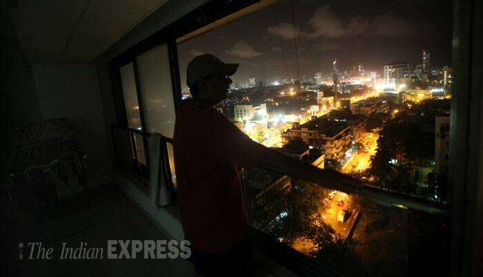 A man looks at the illuminated streets of Mumbai from his Campa Cola flat balcony, where the electricity supply was cut off. (Source: Express photo by Pradip Das)