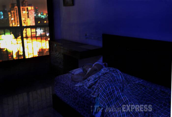 A man is seen sleeping in the dark in his flat at Campa Cola Compound. (Source: Express photo by Pradip Das)