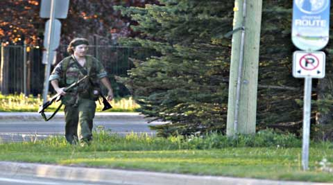 A heavily armed man that police have identified as Justin Bourque walks on Hildegard Drive in Moncton. (Source: AP)