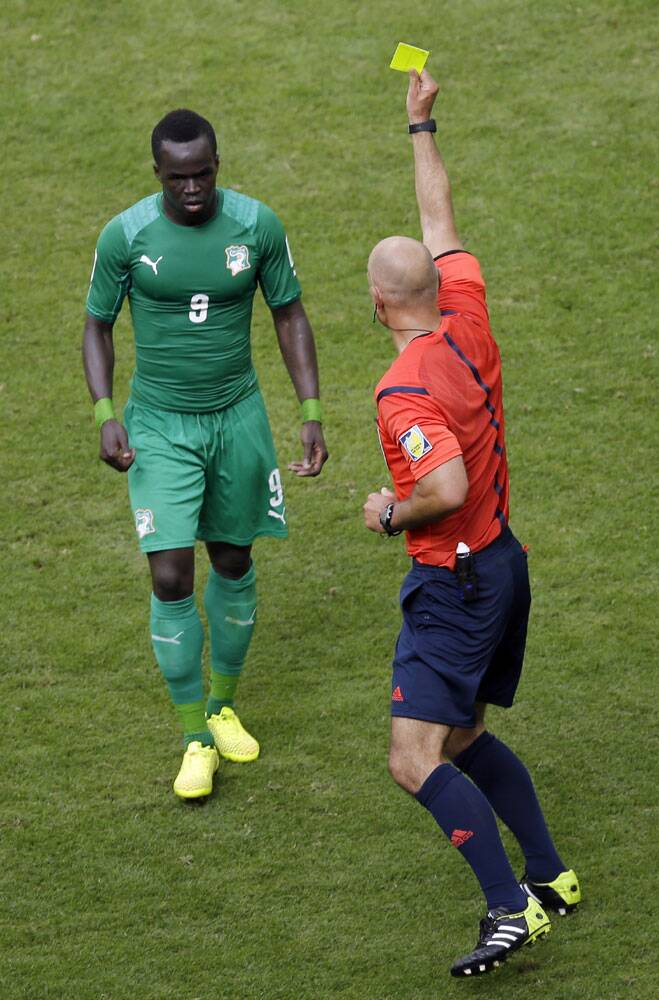 Referee Howard Webb from England shows a yellow card to Ivory Coast's Cheik Tiote for a tackle. (Source: AP)