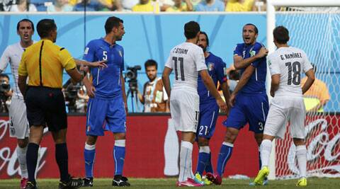 Chiellini pulling down his shirt and indicating to the referee the bite mark. But the latter paid no heed and allowed play. (Source: Reuters)