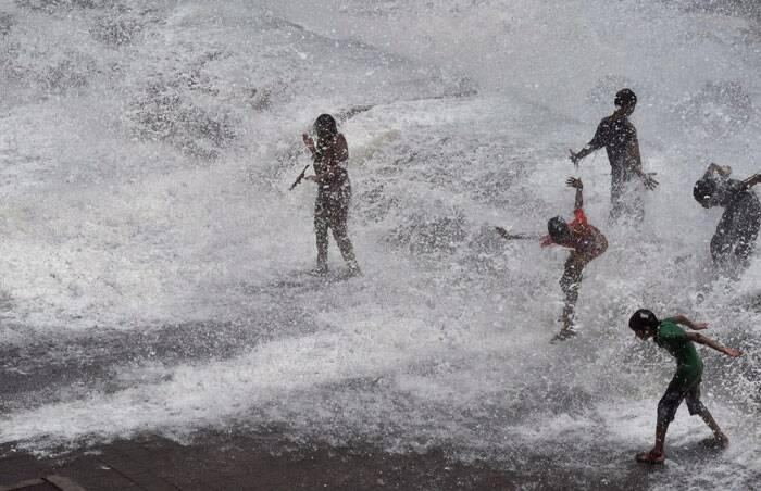 People enjoy high tide at Marine drive in Mumbai on Friday. (Source: PTI)