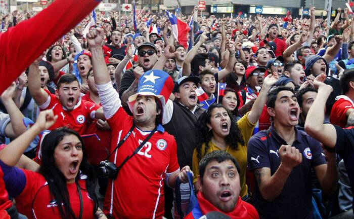 Estatic: Chilean fans cheer after their team beat reining world champs Spain 2-0, knocking them out of the tournament. (Source: Reuters)