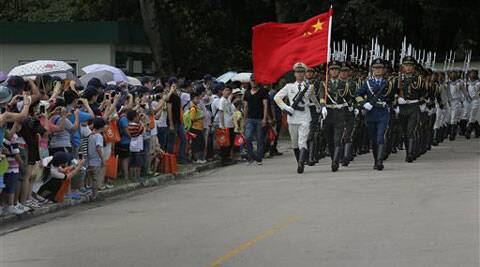 Chinese People's Liberation Army soldiers march with a Chinese national flag at a military base during an open day event of the PLA in Hong Kong, Sunday. (Source: AP)