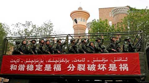 At least 380 people have been detained in the last month in a sweeping crackdown on violence in Xinjiang. In file photo, armed paramilitary policemen ride on a truck during an anti-terrorism oath-taking rally at the Grand Bazaar in Urumqi, in northwestern China's Xinjiang region.