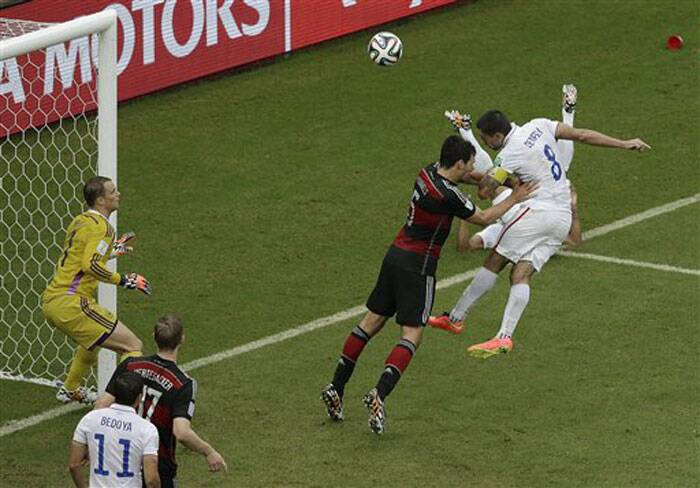 United States' Clint Dempsey heads the ball towards the goal past Germany's Mats Hummels and  goalkeeper Manuel Neuer. The ball went high and Dempsey could not score. (Source: AP)