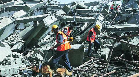 Rescue workers search for survivors in the rubble of the collapsed building, Sunday.