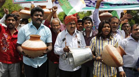 Supporters of Congress party shout slogans as they carry a bucket and earthen pots outside the ruling Bharatiya Janata Party (BJP) office in Delhi. (Source: AP)