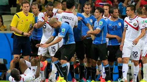 Uruguay's Maxi Pereira reaches out to Costa Rica's Joel Campbell, left, after he fouled him. (Source: AP photo)