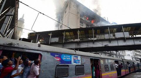 Train passengers looking at a fire that broke out on the fifth floor of the new administrative building of the Central Railway at DN Road in Mumbai on Friday. (Source: PTI)