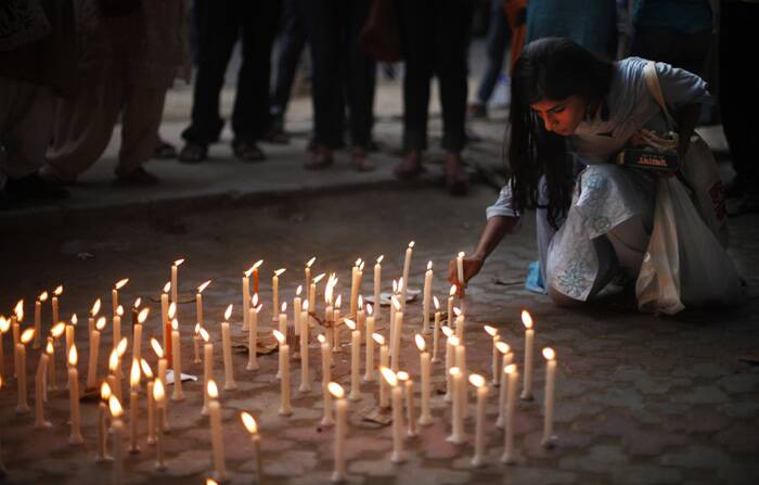 An activist places a candle on a pavement during a candle lit vigil to protest against the gang rape of two teenage girls, in New Delhi. (Source: AP)