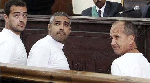 Al-Jazeera English producer Baher Mohamed, left, Canadian-Egyptian acting Cairo bureau chief Mohammed Fahmy, center, and correspondent Peter Greste, right, appear in court along with several other defendants during their trial on terror charges, in Cairo, Egypt.  (Source: AP)