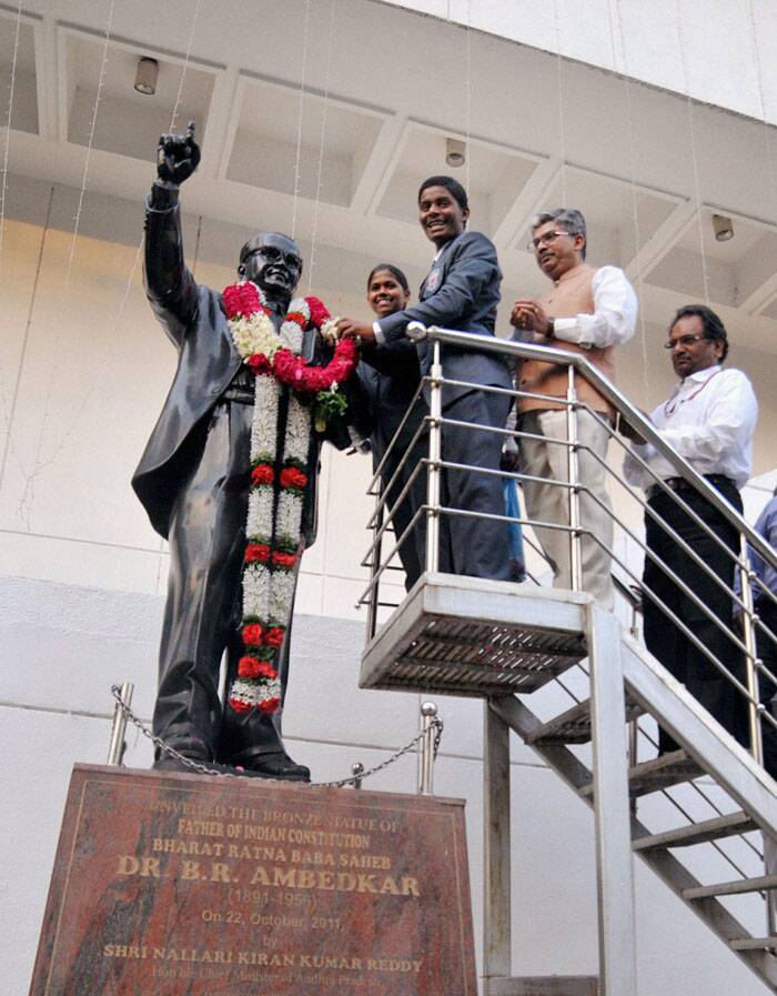 Malavath Poorna and S. Anand Kumar garland a statue of Bhim Rao Ambedakar,who scaled Mount Everest during a ceremony in New Delhi on Thursday. (Source: PTI)
