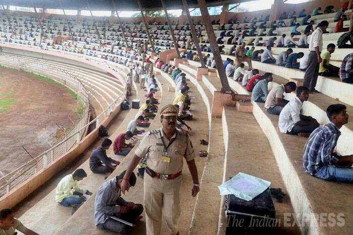 A policeman keeps a watch as candidates take the written test for police recruitment exam in Mumbai. (Source: Express photo by Deepak Joshi)