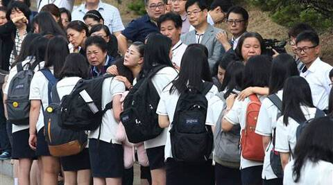 Students who survived the sinking of a ferry Sewol are comforted by parents of their friends who lost their lives in the disaster as they make their way back for their first class since the disaster in Ansan, South Korea.