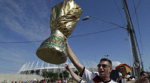 A German soccer team fan holds a mock World Cup trophy as he arrives for the group G World Cup soccer match between Germany and Ghanao on Saturday. (Source: AP)