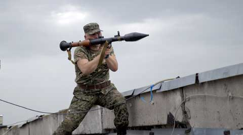 A pro-Russian rebel prepares to fire a rocket propelled grenade during clashes as they attack a border guard base held by Ukrainian troops on the outskirts of Luhansk. (AP)