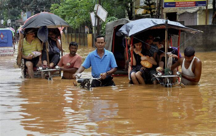Rickshaw pullers wade through a waterlogged street after heavy rains in Guwahati on Friday. (Source: PTI)