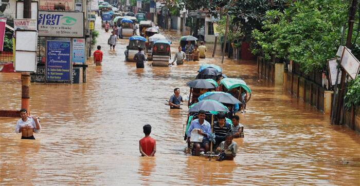 Rickshaw pullers and people wade through a waterlogged street after heavy rains in Guwahati on Friday. (Source: PTI)