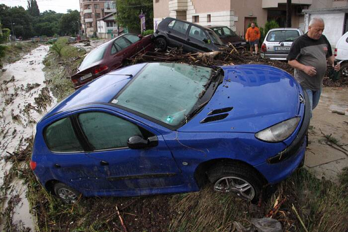 Residents walk past piled up cars hit by severe flooding in the town of Varna, Bulgaria. (Source: AP)