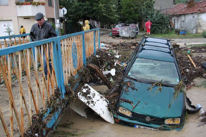 A man walks past debris and cars swept away by severe flooding in the town of Varna, Bulgaria on Friday. (Source: AP)