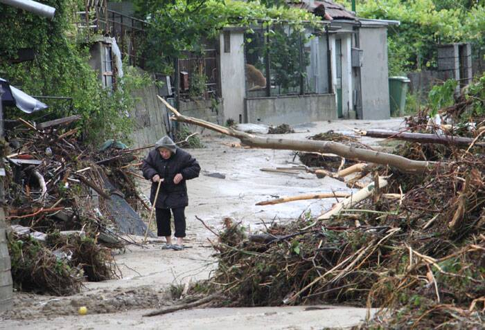An elderly woman makes her way over the flooded street in the town of Varna, Bulgaria on Friday. (Source: AP)