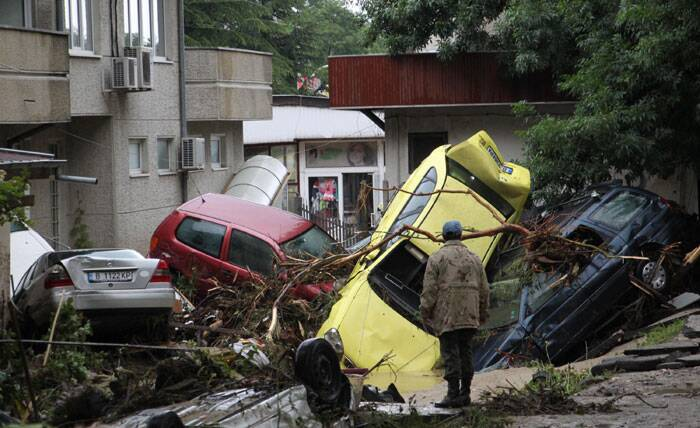 A man looks over piled up cars swept away by severe flooding in the town of Varna, Bulgaria. (Source: AP)