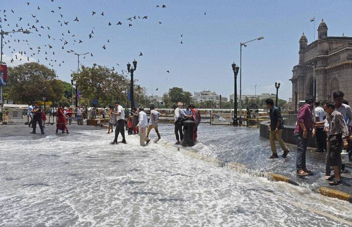 People walk cautiously at a road inundated after a high tide near the Gateway of India in Mumbai on Friday. (Source: PTI)