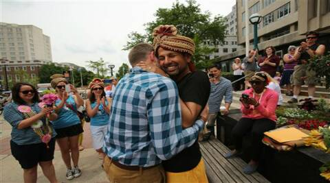 Todd Kinsman, 28, left, and Ravi Manghnani, 37, hug after getting married by their friend, Michele Ritt, a Universal Life Minister, outside the City-County Building the day after the ban on same-sex marriage was struck down in Wisconsin, in Madison, Wis., Saturday, June 7, 2014.