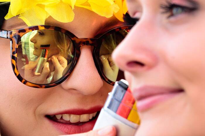 Time for some colour: A german fan paints her friend's cheek with the colours of their flag. (Source: AP)