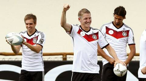 Germany's Bastian Schweinsteiger gestures as he walks in front of his team mates Philipp Lahm (L) and Sami Khedira (R) during a training session. (Source: Reuters)