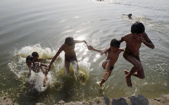 Boys jump in the River Ganga to beat the heat on a hot day in Allahabad on Saturday. (Source: PTI)