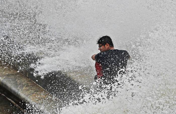 A youth enjoys a high tide at Marine Drive in Mumbai on Thursday. (Source: PTI)