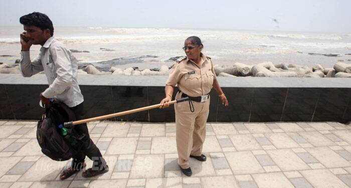 A policewoman makes a man leave after he was caught sitting at the seaside. (Source: Express Photo by Prashant Nadkar)