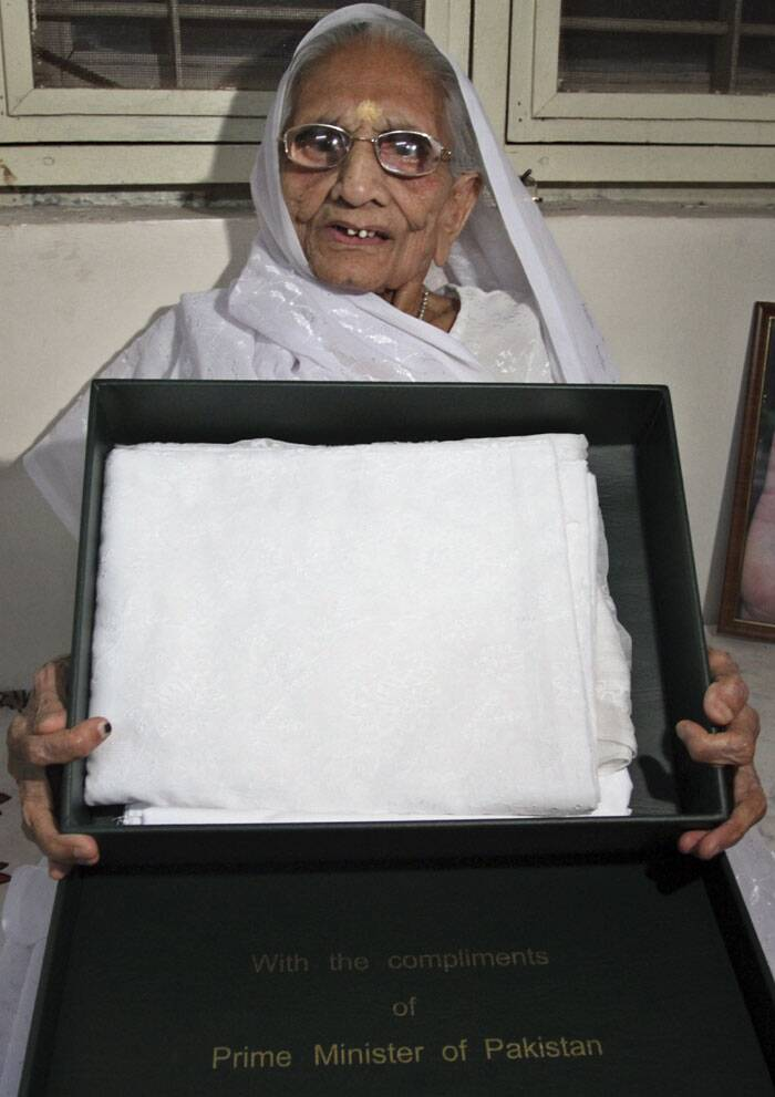 Hiraben, mother of PM Narendra Modi, shows a white sari gifted to her by Pakistan Prime Minister Nawaz Sharif in Gandhinagar. <br /> Earlier Modi had gifted a shawl to the Pakistani leader's mother. (Source: AP)