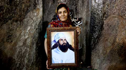 A Zoroastrian woman holds a portrait of prophet Zoroaster in Chak Chak, a mountain shrine, some 600 kilometers (370 miles) southeast of the capital Tehran, Iran. (AP)