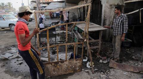 Iraqi civilians inspect the aftermath and remove debris in the site of a car bombing at an industrial area in Baghdad's eastern Ur neighborhood, Iraq, Sunday, June 8, 2014. (AP)