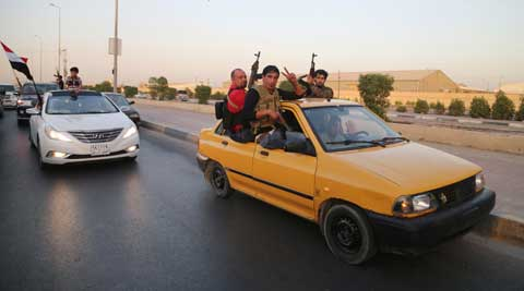 Shiite tribal fighters raise their weapons and chant slogans against the al-Qaida-inspired Islamic State of Iraq and the Levant (ISIL) in Basra, Iraq. (AP)