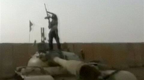 A militant standing on top of a tank holds a gun aloft at a military compound abandoned by the Iraqi military near Tikrit in Salah al-Din province, Iraq. (Source:AP)