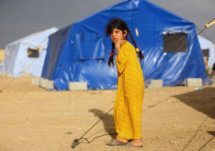 A refugee girl stands perplexed outside the refugee camp. (Source: AP)