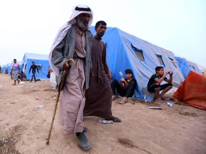 An eldery man walks down the refugee camp with his family. (Source: AP)
