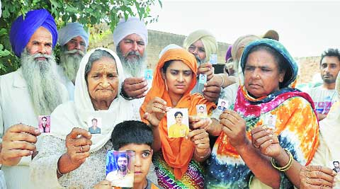 Family members of lndians trapped in Iraq with their photographs at a village near Devigarh in Patiala on Friday. Source: PTI