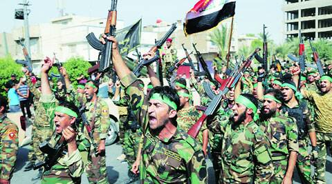 "Volunteers of newly formed ""Peace Brigades"" raise their weapons and chant slogans against the ISIL during a parade in Baghdad Saturday."